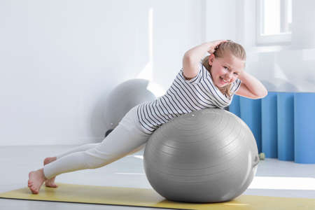 Smiling girl in striped shirt doing exercise on grey ball during rehabilitation in hospital room