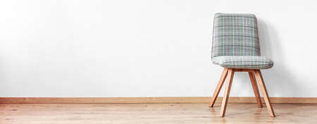 Lone grey chair standing on a wooden floor in an empty room with white wall Imagens