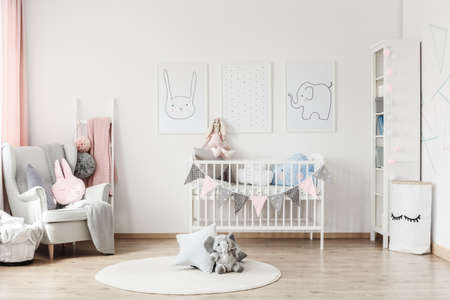 Plush toy and pillow on white round carpet in babys room with grey armchair and posters on wall