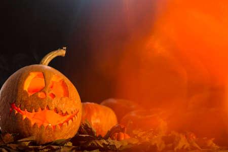 Halloween pumpkin head with autumn leaves on a dark background