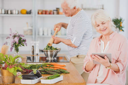 Senior woman uses tablet while her husband is preparing fresh and healthy salad in kitchen