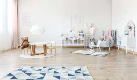 Designer white lamp above small table with plush bear on chair in babys room with rocking horse