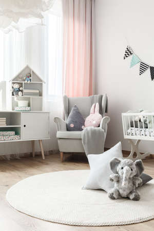 Grey elephant toy and star pillow on white round carpet in baby's room with grey armchair and cupboard