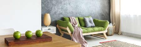 ピンクの毛布と棚の上にランプと自然のリビング ルームでコンクリートの壁に緑のソファの上灰色枕