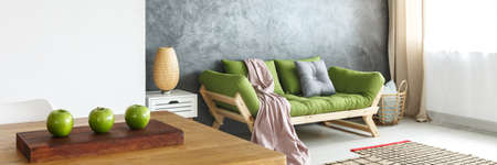 Pink blanket and grey pillow on green sofa against concrete wall in natural living room with lamp on shelf