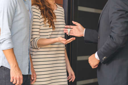 フラットの購入者にキーを与える黒のスーツで売り手のクローズ アップ 写真素材