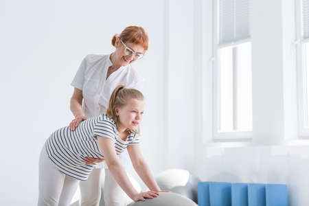 Physiotherapist improving posture of girl with her hands on a grey ball for corrective exercises