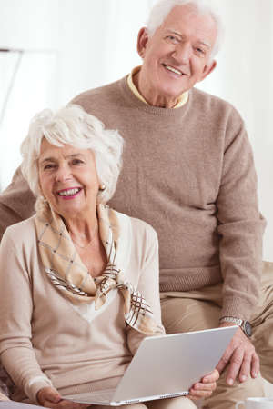 Couple of happy elder people uses computer together while sitting at home Stock Photo