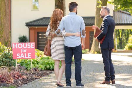 """Makelaar in onroerend goed en klanten staan ??naast bord met opschrift """"huis te koop"""""""