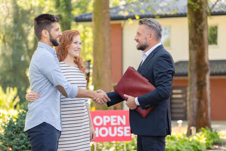 Real estate agent welcoming young smiling couple and inviting to presentation of house