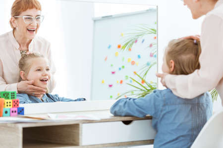 Girl with speech defect practicing with speech therapist in classroom with whiteboard Stock Photo