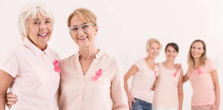 Drie jonge vrouwen staan achter twee gelukkige en zelfverzekerde ouderen. Borstkanker concept