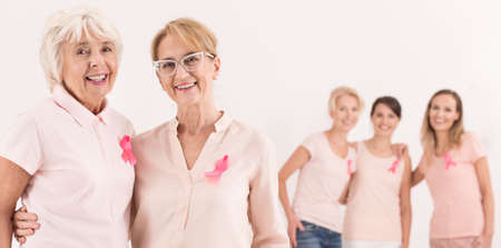 Three young women stand behind two happy and confident elderly. Breast cancer concept