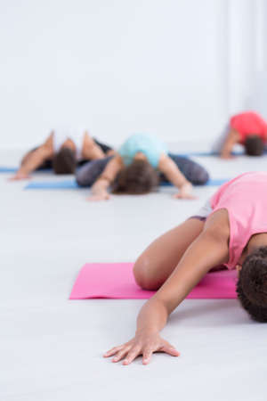 in low spirits: Practitioner is concentrating on yoga exercise while lying on pink mat