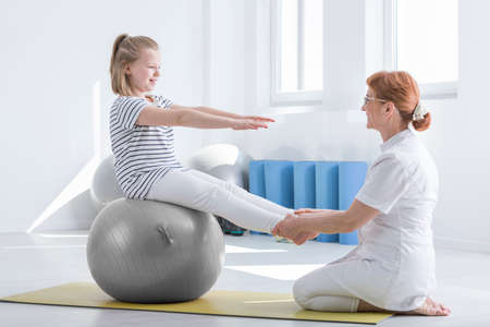 Girl in striped shirt sits on grey ball with arms and legs stretched forward during rehabilitation