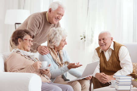 Group of senior friends converses while using laptop in living room