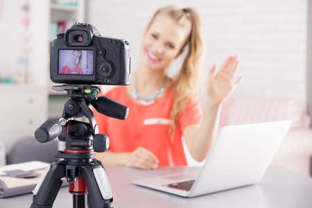 Vlogger recording herself with camera placed on desk with laptop