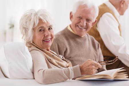 幸せな高齢者が明るい部屋で本を読んでいる妻を見てください。 写真素材