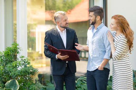 Adviseur van onroerend goed markt presenteren aanbod van appartementen in de buurt van een jong koppel Stockfoto - 87392577