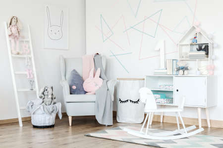 Pink pillow on grey armchair and white rocking horse on carpet in scandi kids room with cupboard
