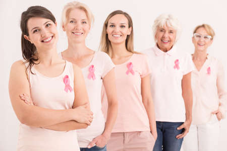 Women wearing pink shirts and breast cancer ribbons on white background 版權商用圖片