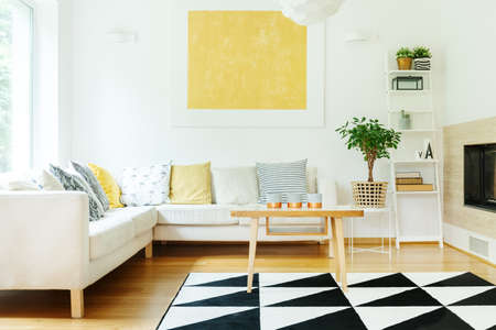 Kaarsen op houten lijst en beige bank met gevormde kussens in warm binnenland met installatie op kruk en het gele schilderen op muur Stockfoto