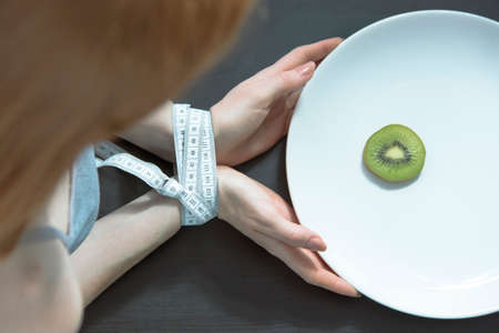 Woman with an eating disorder, and her hands bound by tape-measure limiting her dinner to a kiwi