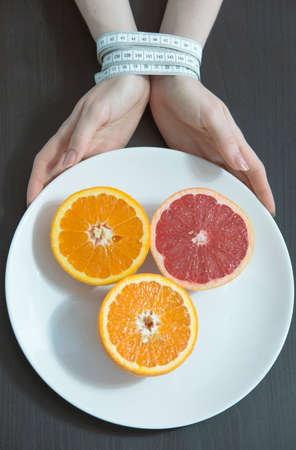 Two hands bound by a tape-measure, holding a platter of orange and grapefruit in a concept of eating disorder