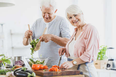 おばあちゃんカット コショウ、白いキッチンで一緒に調理中におじいちゃんのミックス野菜サラダ 写真素材