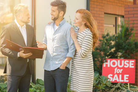 Young couple negotiating with agent terms and conditions of property purchase agreement