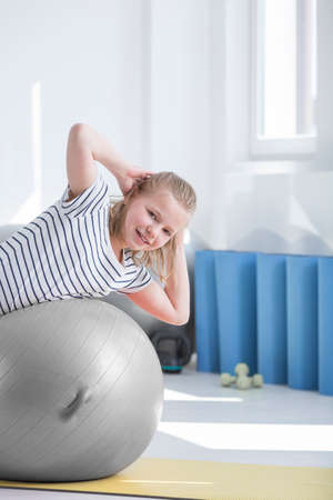 blonde girl doing exercise on grey ball and yellow mat in room for corrective exercises