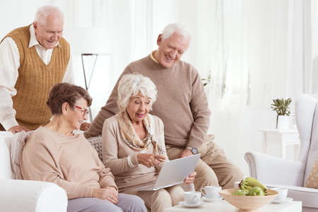 Group of elder friends are using laptop while sitting in white living room Stock Photo