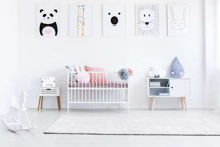 Girl's bedroom with rocking horse and bed with pink pillows against wall with animal posters gallery