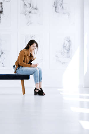 Young woman sitting on stool and reading guidebook while visiting art gallery Stock Photo