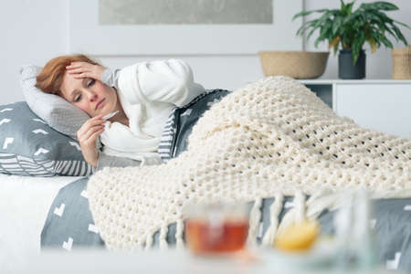 Ill woman lying in bed looking at thermometer suffering from seasonal flu and infectious disease Stock Photo