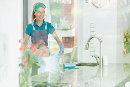 Smiling woman working in house cleaning service holding new garbage bag in fresh modern kitchen interior