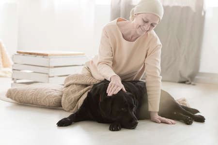 Senior sick woman stroking dog while sitting on floor at home