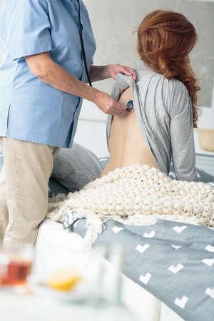 Doctor auscultating paciente enfermo con gripe y fiebre con estetoscopio durante la visita en el hogar