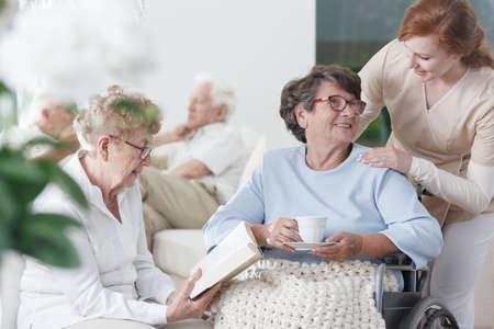 양로원의 휴게실에서 시간을 함께 보내는 두 노인 숙녀