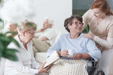 Two elder ladies in glasses spending time together in common room of nursing home