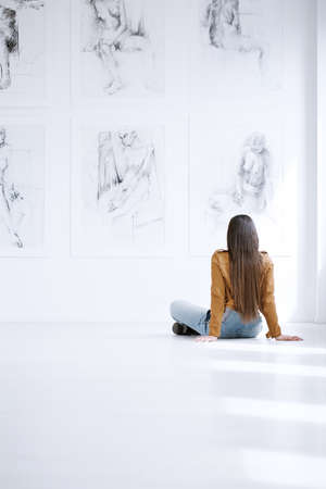 Woman sitting on floor and looking at drawing collection on white wall in museum