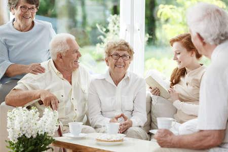 高齢者の患者に共通の部屋を読んで若い白人の乳母
