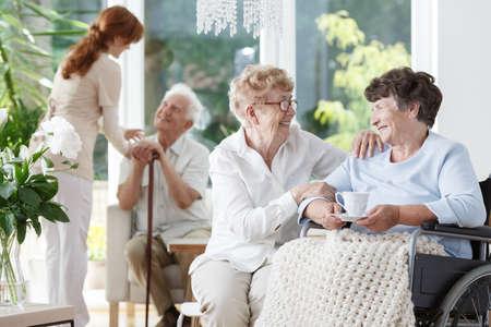 Donna anziana con gli occhiali in visita al suo amico disabile a casa dell'anziano