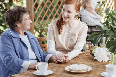 Caucasian caretaker sitting by wooden garden table and talking to older woman in glasses Stock Photo
