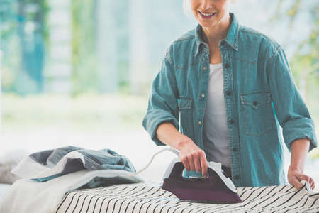 Housework concept, close-up photo of happy woman ironing clothes on the ironing board with electric iron wearing casual jean shirt at home Stock Photo