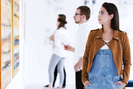 Casual dressed woman observing paintings while visiting art gallery Stok Fotoğraf