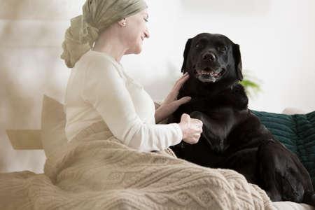 犬のがんの病気の女性に自宅のソファに一緒に座って足を与える