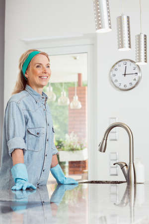 Spring cleaning concept, beautiful middle-aged female housekeeper smiling enjoying her fresh clean house posing in her kitchen wearing rubber gloves