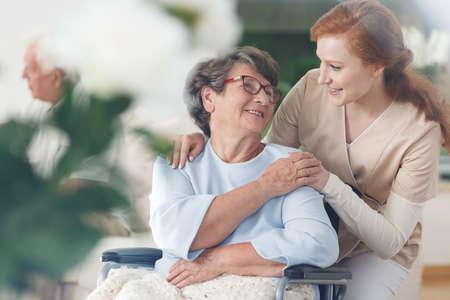 Oude dame in glazen die in een rolstoel zitten en bij haar verpleegster glimlachen
