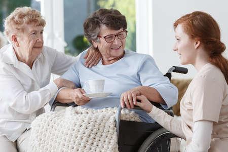 휠체어 및 그녀의 방문 자매 그녀의 환자에게 이야기하는 제복을 입은 백인 간호사 스톡 콘텐츠